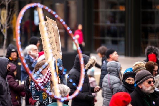 "A LED peace sign is seen in the crowd during a protest organized by ""Veterans for Peace"" in opposition to war in Iran, Saturday, Jan. 4, 2020, in Iowa City, Iowa."