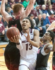 Bellarmine guard Dylan Penn squeezes between Lewis center Brandon McCombs, left, and Lewis guard Artese Stapleton, right, to score.