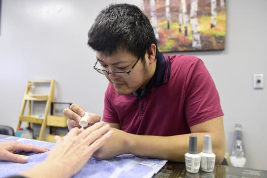 Jason Dang of Spicy Nails & Spa in Galion helps a customer Saturday afternoon.