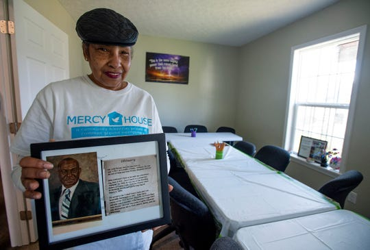 Mary Boone holds a framed obit of her uncle John Wesley McCree in his former home, that is now the the Pathway House in the Washington Park neighborhood in Montgomery, Ala., on Saturday January 4, 2020.