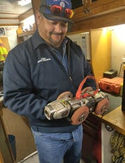 Las Cruces Utilities' Lonnie Orona, wastewater collections system inspector, holds the little robot truck that travels up and down city sewers seeing inside more than 500 miles of underground sewer lines.