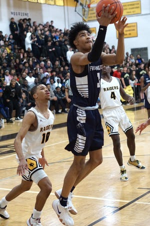 Jaden Akins tries to lay one in during Farmington's game against in-district rival North Farmington. Against Birmingham Tuesday, the Falcons netted its second victory of the season.