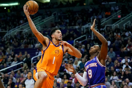 Phoenix Suns guard Devin Booker (1) shoots over New York Knicks guard RJ Barrett during the second half of an NBA basketball game Friday, Jan. 3, 2020, in Phoenix. The Suns won 120-112. (AP Photo/Rick Scuteri)