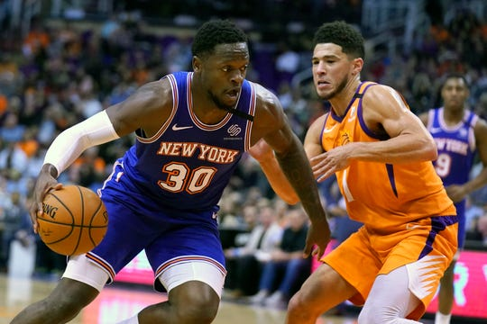 New York Knicks forward Julius Randle (30) drives against Phoenix Suns guard Devin Booker in the first half during an NBA basketball game, Friday, Jan. 3, 2020, in Phoenix. (AP Photo/Rick Scuteri)