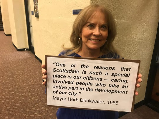 Janet Wilson, chair for the Committee to Protect Old Town Scottsdale, stands with a sign quoting former Mayor Herb Drinkwater after dropping off signatures for a referendum that would send the Southbridge II project to a vote.