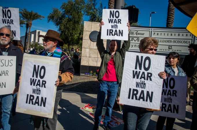 People protest the Trump administration's killing of a top Iranian general and decision to send 3,000 more soldiers to the Middle East on the corner of Camelback Road and 24th Street in Phoenix on Jan. 4, 2020.