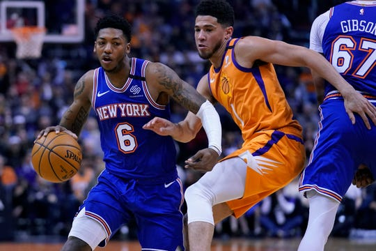 New York Knicks guard Elfrid Payton (6) drives against Phoenix Suns guard Devin Booker in the first half during an NBA basketball game, Friday, Jan. 3, 2020, in Phoenix. (AP Photo/Rick Scuteri)