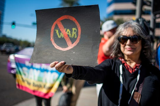 Amira de la Garza holds an anti-war sign in protest of the Trump administration's killing of a top Iranian general and decision to send 3,000 more soldiers to the Middle East on the corner of Camelback Road and 24th Street in Phoenix on Jan. 4, 2020.