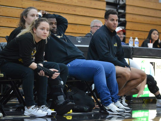Enterprise leading scorers Alissa Terras, left, and Abby Shoff, front left center, remain sidelined with injuries as assistant coach Ky Strickler and coach Anthony Williams look on during Friday's game against Modoc.