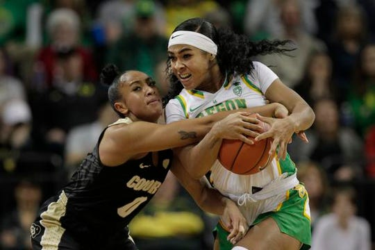 Colorado's Quiessa Caylao-Do, left, tries to get the ball from Oregon's Minyon Moore during the second quarter of an NCAA college basketball game in Eugene, Ore., Friday, Jan. 3, 2020. (AP Photo/Chris Pietsch)