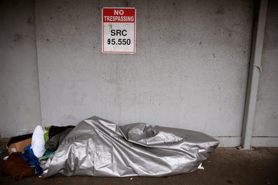 "A person sleeps while wrapped in a tarp with ""Shame on Mayor Bennett"" written on it on the west side of the Rite Aid in downtown Salem on Jan. 2, 2020. A city ordinance doesn't allow tents to be set up, but people can currently sleep on sidewalks."