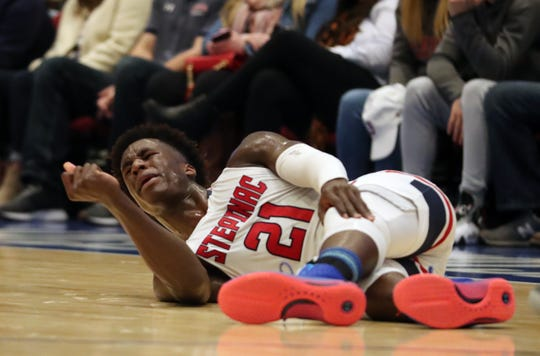 Stepinac's Adrian Griffin Jr. (21) grabs his leg in pain after going down in the second half with an injury during game against Iona in the 3rd annual Crusader Classic at the Westchester County Center in White Plains Jan. 3, 2020. Stepinac won the game 62-54.