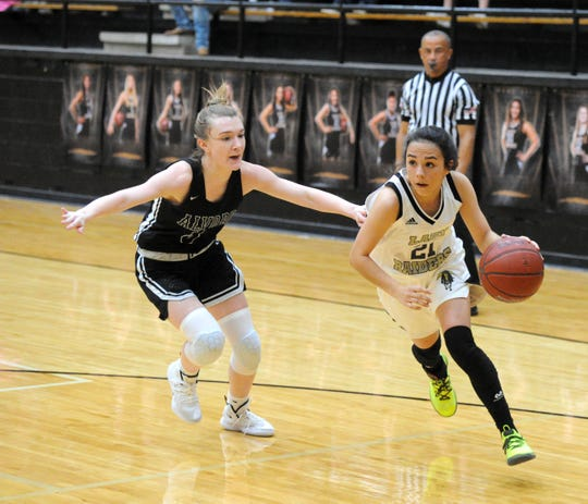 Rider's Ashlynn Knight (21) drives past Alvord's Katie Slaten in a non-district matchup Friday, Jan. 3, 2020, at Rider Fieldhouse.