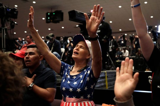 Wanda Albritton raises her ams in prayer during a Trump rally for evangelical supporters at the King Jesus International Ministry church on Jan. 3, 2020, in Miami.