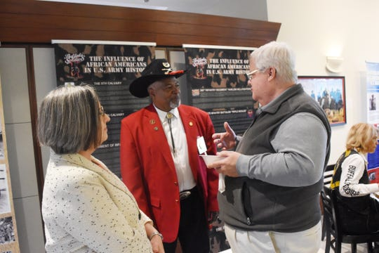 """Catherine Pears (left), Alexandria Museum of Art executive director, Joe Tillmon, president of the Buffalo Soldiers Historical Society and Steve Norman talk at the opening reception and program for """"A Legacy of Honor and Valor"""", a traveling exhibit detailing the history of African-Americans in the U.S. Military now on exhibit at the Alexandria Museum of Art."""