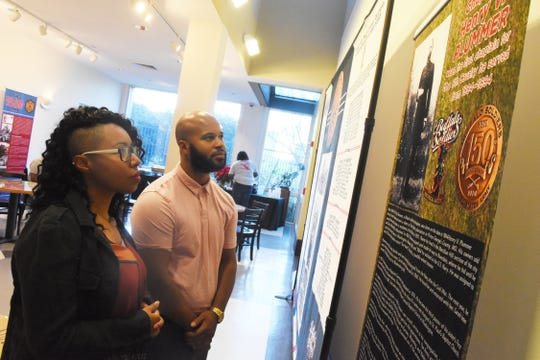 """Princella Talley (left) and Harry Hayes look at """"A Legacy of Honor and Valor,"""" an exhibit detailing the history of African-Americans who served in the U.S. military currently on exhibit at the Alexandria Museum of Art through Feb. 22."""
