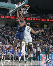 Monmouth's Nikkei Rutty scores inside against Siena's Sammy Friday during the Hawks' 75-72 loss in Albany, New York.