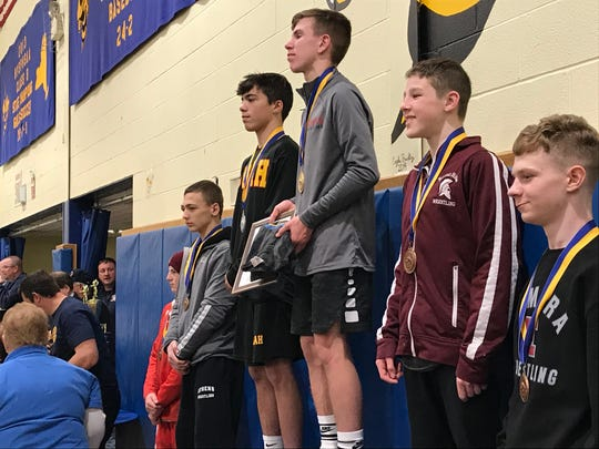 Chenango Forks' Tyler Ferrara stands at the top step of the awards podium after winning the 106-pound title in the Ross Cordell Rotary Tournament on Saturday at Oneonta High.