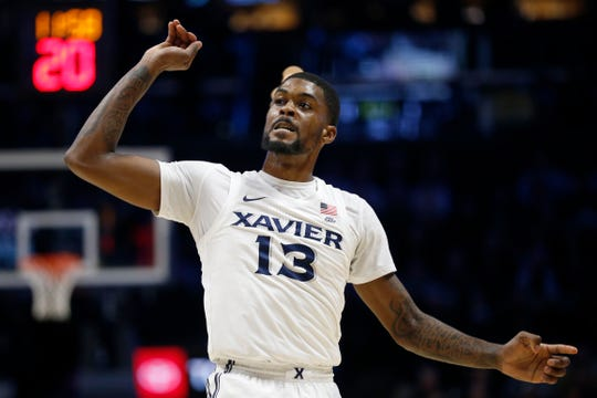 Xavier Musketeers forward Naji Marshall (13) follows through as he sinks a three point shot in the first half of the NCAA Big East game between the Xavier Musketeers and the St. John's Red Storm at the Cintas Center in Cincinnati on Sunday, Jan. 5, 2020. Xavier led 34-32 at halftime.