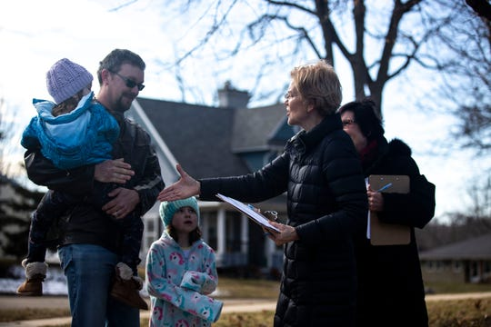 U.S. Sen. Elizabeth Warren, D-Mass., gets a commit to caucus card signed by Travis Dontje, accompanied by his daughters Krysten and Gracie, on Sunday, Jan. 5, 2020, in Maquoketa, Iowa.