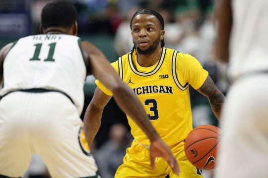 Michigan guard Zavier Simpson is defended by Michigan State forward Aaron Henry during the first half Jan. 5, 2020.