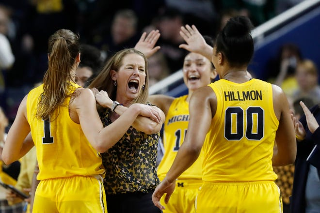 Michigan coach Kim Barnes Arico, second from left, celebrates the win over Michigan State with guard Amy Dilk, left, and forward Naz Hillmon during the second half of U-M's 89-69 win over MSU on Sunday, Jan. 5, 2020, at Crisler Center.