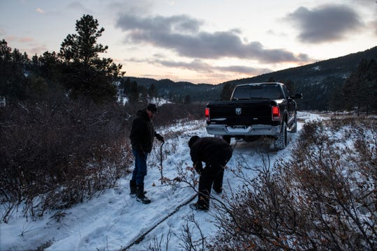 Richard King, 70, and his brother, Brent, right, work to pull Richard's truck out of the mud on the family ranch near Zortman, Mont., on the Fort Belknap Indian Reservation on Sunday, Dec. 8, 2019.
