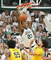 Michigan State's Xavier Tillman slams home a dunk off a pass from teammate Cassius Winston in the second half.
