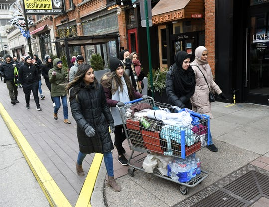 Aamna Hafeez, 26, of Detroit, Nassrine Naim, 24, of Dearborn, and Zainab Hammoud, 26, of Dearborn push a cart full of items as volunteers from 1Humanity give out food, socks, jackets and other clothing to people in need in Detroit on Jan. 5, 2020.