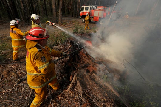 Firefighters battle a fire near Bendalong, Australia, Friday, Jan. 3, 2020.