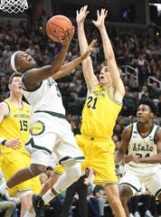 Michigan State's Cassius Winston goes under the basket and puts up a shot with Michigan's Franz Wagner defending in the first half.
