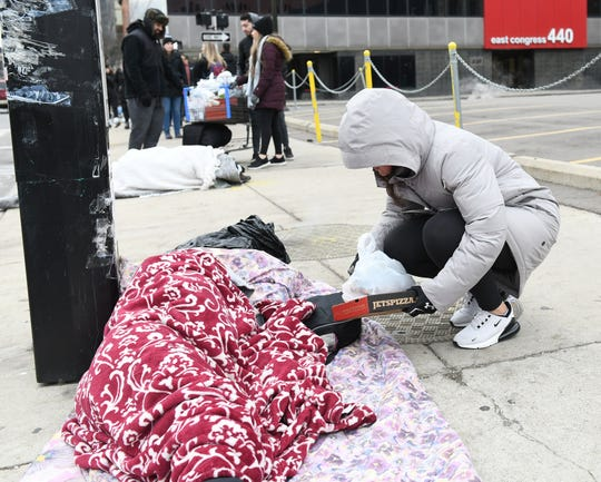 Sara Dervishi, 25, of Detroit leaves a pizza and a bag of clothing with a person lying on the sidewalk as volunteers from 1 Humanity Drive give out food, socks, jackets and other clothing to people in need in Detroit on Jan. 5, 2020.