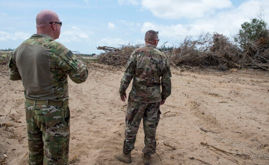 U.S. Air Force Lt. Col. Vance Goodfellow, left, 475th Expeditionary Air Base Squadron (EABS) commander, and U.S. Army Lt. Col. Todd Martin, safety officer assigned to the Combined Joint Task Force - Horn of Africa Safety directorate, look at trees that are being cleared during a battlefield circulation site visit Feb. 24, 2018, at Camp Simba, Manda Bay, Kenya.