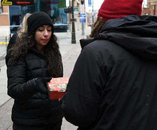 Sara Nasser, 26, of Dearborn gives a pizza to an unidentified man in the Greektown neighborhood of Detroit on Jan. 5, 2020