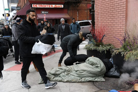 Nabeel Shahzad, left, 31, of Canton and Asim Ghani, 22, of Sterling Heights give out bags of clothing and blankets as volunteers from 1Humanity give out food, socks, jackets and other clothing to people in need in Detroit on Jan. 5, 2020