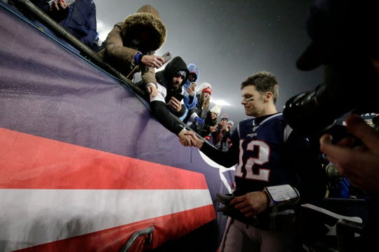 New England Patriots quarterback Tom Brady shakes hands with a fan as he leaves the field after losing an  AFC wild-card playoff football game to the Tennessee Titans on Saturday.