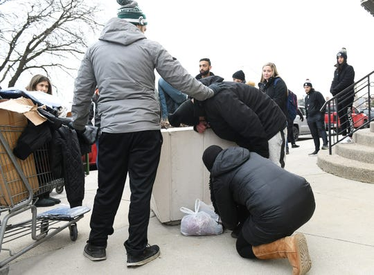 """Ali Bazzi, 26, of Dearborn, left, tries to comfort a man who apologized after Bazzi after traded shoes with him. Bazzi says, """"I don't know how he was walking around in those. I have more shoes at home."""""""