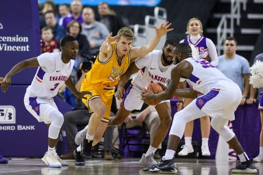 Evansville's John Hall (35) gains control of a loose ball as Evansville's Jawaun Newton (3), Valparaiso's Ben Krikke (23) and Evansville's K.J. Riley (33) prepare to dive for it during the second half at Ford Center in Evansville, Ind., Saturday, Jan. 4, 2020. The Purple Aces fell 81-79 to the Crusaders in overtime.