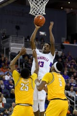 Evansville's DeAndre Williams (13) goes up for a shot over Valparaiso's Nick Robinson (25) and Valparaiso's Donovan Clay (5) during the second half at Ford Center in Evansville, Ind., Saturday, Jan. 4, 2020. The Purple Aces fell 81-79 to the Crusaders in overtime.