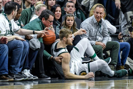 Michigan State's Kyle Ahrens collides with fans while going for the ball during the first half on Sunday, Jan. 5, 2020, at the Breslin Center in East Lansing.