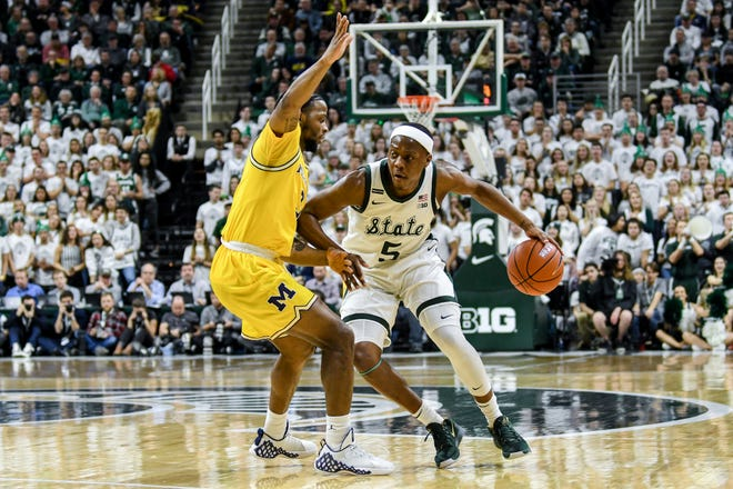 Michigan State's Cassius Winston, right, moves around Michigan's Zavier Simpson during the first half on Sunday, Jan. 5, 2020, at the Breslin Center in East Lansing.