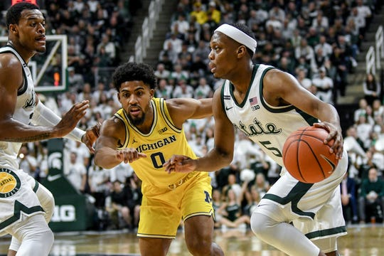 Michigan State's Cassius Winston, right, moves with the ball as Michigan's David DeJulius defends during the first half on Sunday, Jan. 5, 2020, at the Breslin Center in East Lansing.