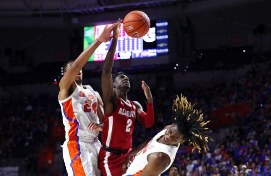 Jan 4, 2020; Gainesville, Florida, USA; Alabama Crimson Tide guard Kira Lewis Jr. (2) gets called for an offensive foul on Florida Gators forward Dontay Bassett (21) during the first half at Exactech Arena. Mandatory Credit: Kim Klement-USA TODAY Sports