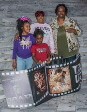 Doe B's daughter Madison Thomas, left, sister Tamara Thomas, center, and mother Shirley Thomas, and a young family friend, front, stand at the Alabama State Capitol steps with images from Doe B's mix tapes.