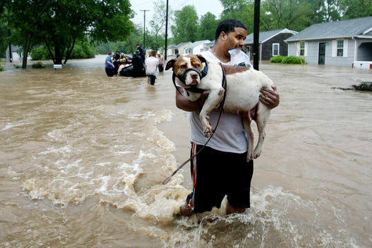 Andrew Hudson carries his dog Sugar after being rescued from floodwaters by boat by the Nashville Fire Department off Winn Road in West Nashville on Sunday, May 2, 2010.
