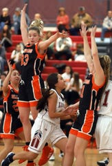 Senior Lady 'Cats Nicole Lopez takes the basketball inside the paint and among the Artesia giants during Saturday's 56-36 home win at Deming High School.