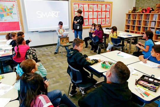 In this undated image, Alicia Ayala, a third grade dual-language teacher at El Camino Real Academy in Santa Fe, helps Ian Lopez Rascon, 8, give a report on lions.