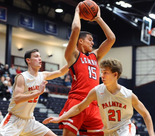 Lebanon's Isaiah Rodriguez (15) makes a move to the basket between Palmyra's Christopher Edwards (22) and Joshua Mark (21) during first quarter action.