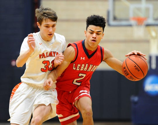 Lebanon's Alexander Rufe (2) is fouled by Palmyra's Roman Byler (33) as he drives to the basket during first quarter action.