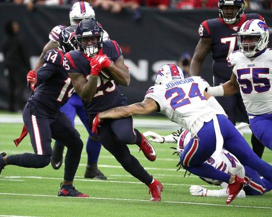 Texans running back Duke Johnson tries to slip this tackle by Bills Taron Johnson.